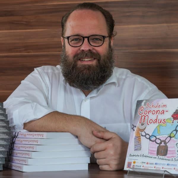 """Herausgeber Tobias Greilich mit seinem neuen Buch """"Schule im Corona Modus"""""""